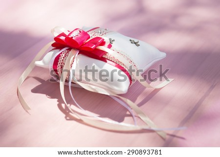 Red rings cushion on table with ribbons - stock photo