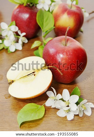 Red ripe apple fruits and apple flower on the wooden table - stock photo
