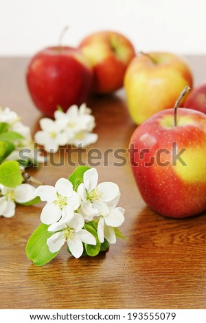 Red ripe apple fruits and white apple flowers on the wooden table - stock photo