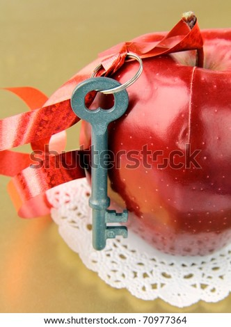 red ripe apple with a key and a red ribbon