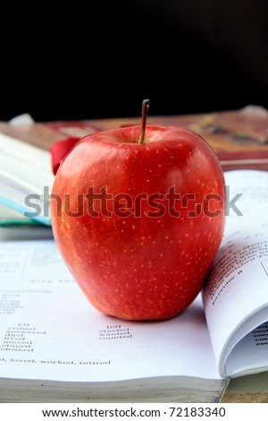 red ripe apple with English textbooks on a black background - stock photo
