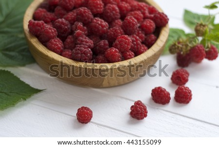 Red ripe raspberries on a white wooden table and a bowl full of raspberries - stock photo