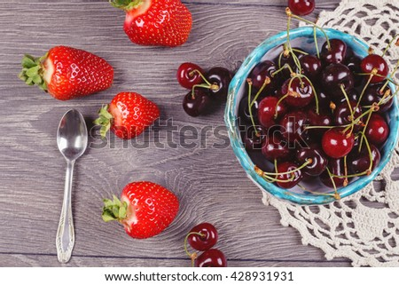 Red ripe strawberries near the cherry bowl on knitted napkin on the gray table. Ripe cherries in handmade clay bowl and strawberries on the background - stock photo
