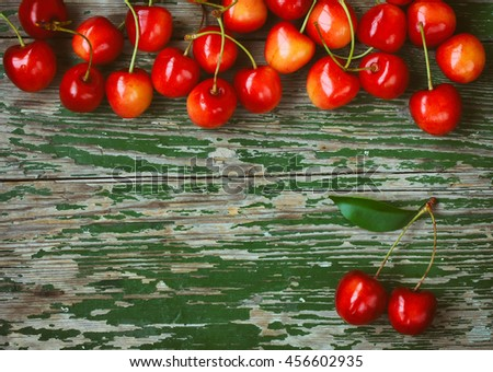 red ripe sweet cherry border on an old rustic wooden table, retro style