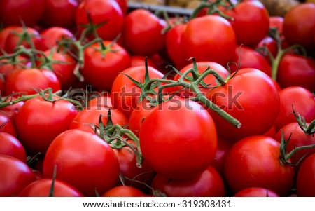 Red ripe tomatoes in a market/basket/carton for sale. Farmer's market.  - stock photo