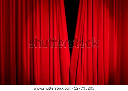 Red rising curtain with a light spot in a theater - stock photo