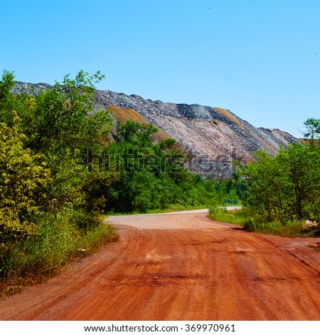 Red road near massive dump of depleted iron ore - stock photo