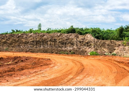 red road with soil wall and bamboo garden that are sky cloud background - stock photo