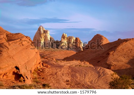 red rock formations against cloudy blue sky.