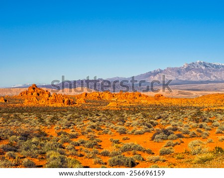 Red rock formations in Valley of Fire State Park, Nevada, USA, with snow-covered mountains in the background, clear blue sky and copy space.. Valley of Fire is in the Mojave Desert in southern Nevada. - stock photo