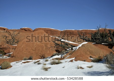 red rock with blue sky and snow - stock photo