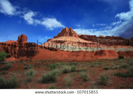 red rocks and blue sky's with clouds with sage brush and red dirt/ The Many Colors of the Desert Mountains - stock photo