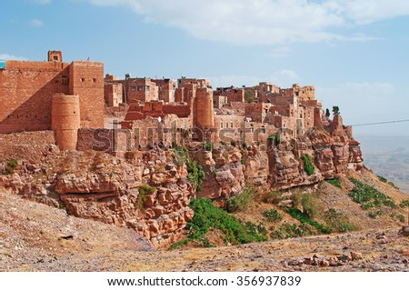 Red rocks and decorated old houses, Kawkaban, the ancient walls, northwest of Sanaâ??a, fortified city, village, Republic of Yemen, daily life - stock photo