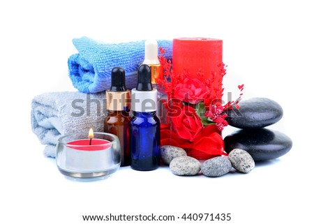 Red romantic candle and spa oil with towel and zen stone isolated on white background - stock photo