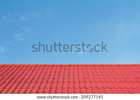 Red roof against blue sky - stock photo