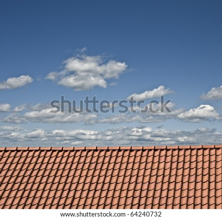 Red roof, cloudy sky - stock photo
