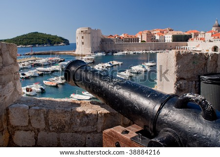 Red roof houses, ancient stone fortress, Dubrovnik old town, Croatia showing boat filled harbor.  Seen over an ancient black cannon. - stock photo