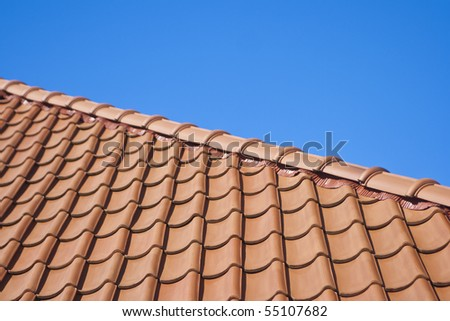 Red roof in the blue sky - stock photo