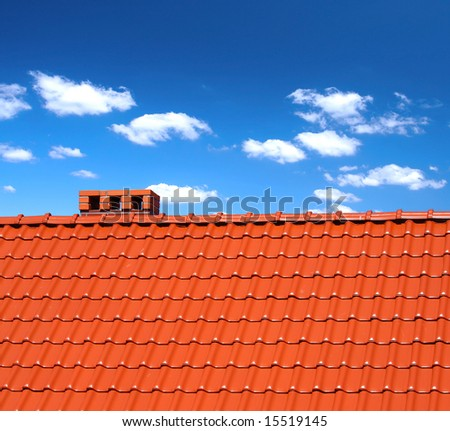 red roofing-tiles with cumulus clouds above - stock photo