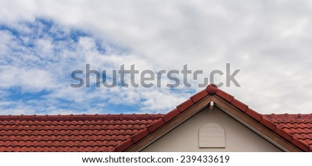 red rooftop against blue sky - stock photo