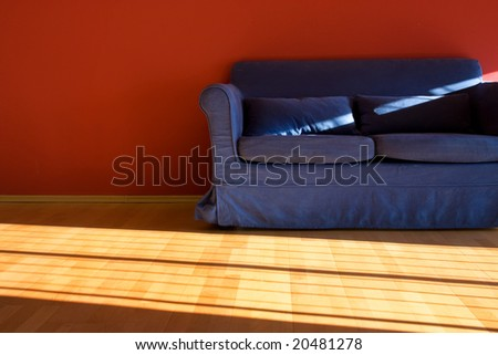 Red room with blue sofa - stock photo