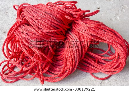 Red rope isolated on concrete background - stock photo