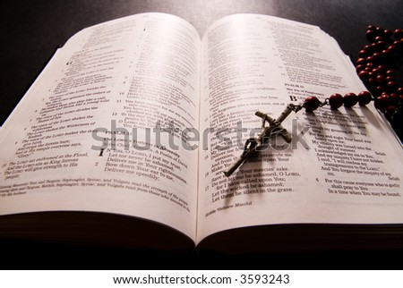 Red rosary and holy bible, shot with dramatic lighting
