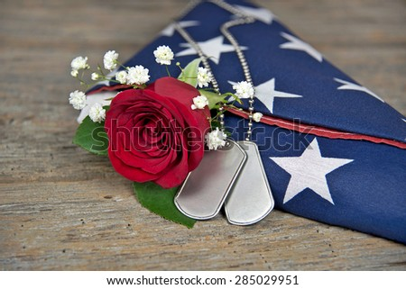 red rose and military dog tags on a folded American flag on rustic wood