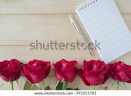 Red rose and one empty notebook and pen on wood background, love concept - stock photo