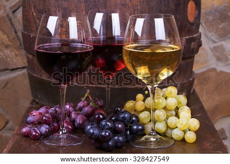 Red, rose and white glasses of wine with grape on old wooden barrel