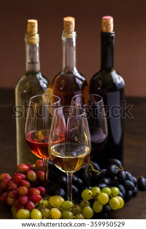Red, rose and white wine bottles with three wineglasses and grapes on brown wood textured table