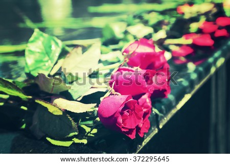 Red rose bouquet laying on mable shrine, vintage tone image. - stock photo