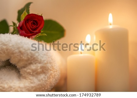 red rose, burning candles and towels in spa composition - stock photo