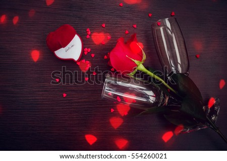Red rose, engagement ring, hearts and champagne glasses over wood with copy space. Valentine's background. Presents for woman on Valentine Day. love, proposal, relations, holidays concept.