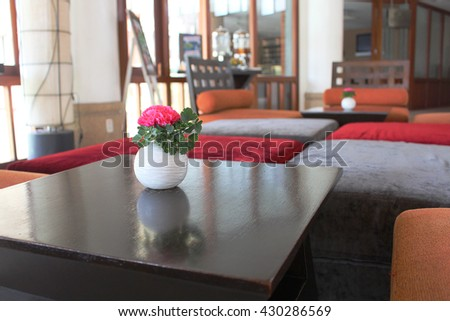 red rose in the small vase put on the table with the seat