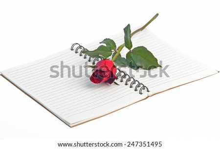 Red rose on a blank notebook isolated on white background - stock photo