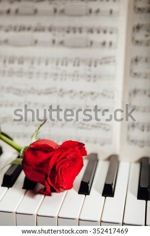 red rose on piano keys and music book - stock photo