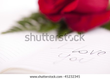 "Red rose on planner, ""I love you"" written on it"