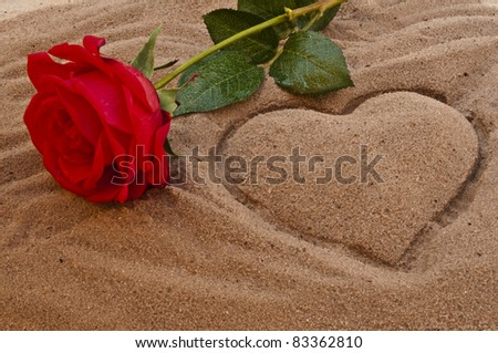 Red rose on the beach with a heart in the sand - stock photo