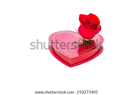 Red rose on the cover of heart shaped gift box, seems rose alive rising from the picture on the box cover, isolated on white background. Macro close up, selective focus. Concept of love from heart.   - stock photo