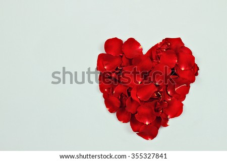 Red rose petals against a blue background with room for copy space.