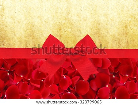 red rose petals and red ribbon with bow over old paper background - stock photo