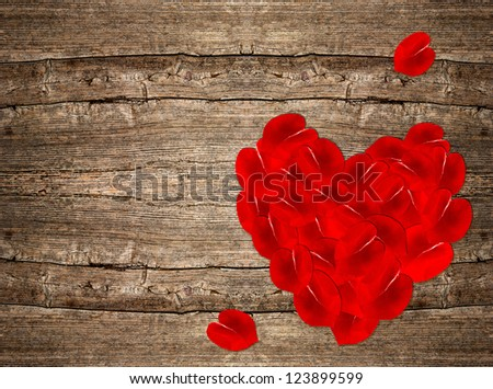 red rose petals in heart shape over rustic wooden backdrop. Valentines Day background - stock photo
