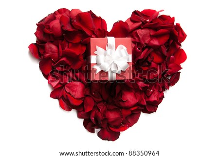Red rose petals making up heart with small giftbox on it - stock photo