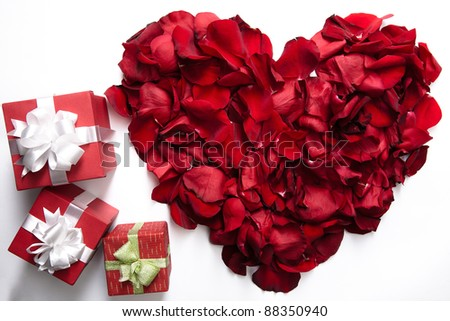 Red rose petals making up heart with small giftboxes near by - stock photo