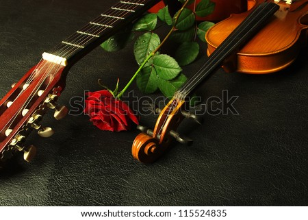 Red rose, violin, guitar. Black background - stock photo