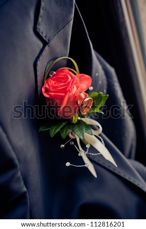 red rose wedding boutonniere on suit of groom. wedding rings