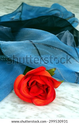 Red rose with a blue scarf on a marble table - stock photo