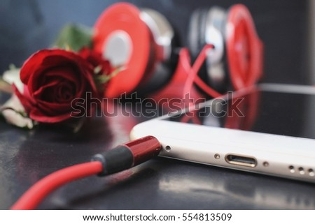 Red rose with earphone and smart phone