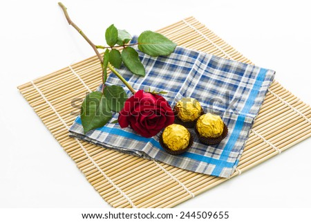 red rose with handkerchief  and chocolate Ball, placemat on white background
